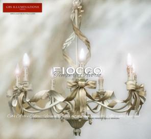 Fiocco in tempera bianco avorio, Lampadario a 7 fiamme con nastri e fiocchi. Tempera anticata.