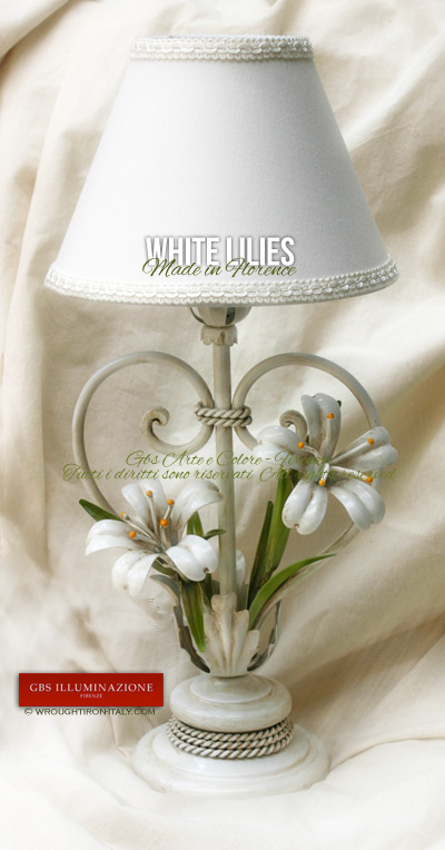 Bedside table lamp in wrought iron with white lilies and an antique white enamel finish. A handmade Italian lampshade with matching colour trimmings.