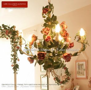 Lampadario Romantico per camera da lettocon rose fiorite. Cinque luci in tempera patinata. Sullo sfondo: Letto Romantico con baldacchino